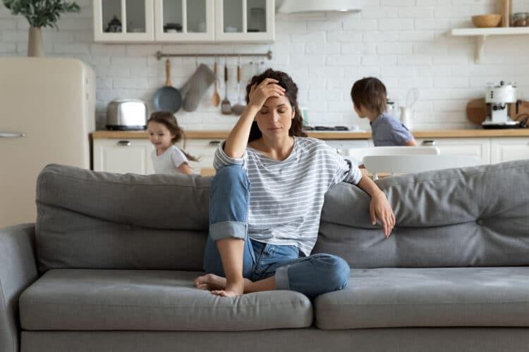 Erschöpfte Mutter sitzt auf Couch, während Kinder zu Hause rennen